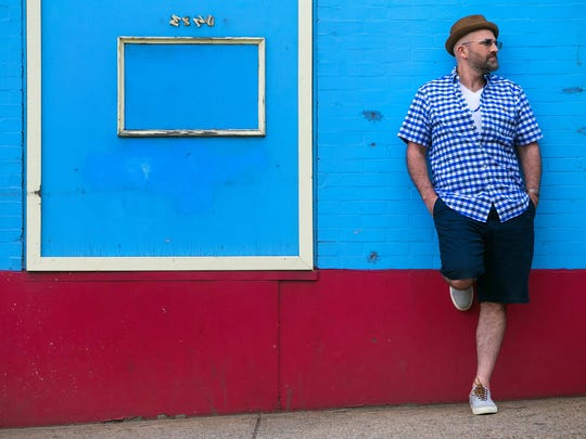 Charles Ebbie Alfree III wears a blue-and white gingham shirt by Polo; knee-length, dark blue shorts from Old Navy; shoes by Polo; cuff bracelet by Olga Ganoudis Designs.