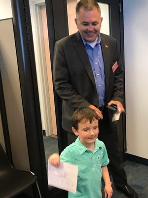 Aiden Page, the nephew of attorney Chris Crowley, holds a campaign petition report after his uncle filed his final batch of campaign petitions for his state attorney candidacy Monday at the Lee County Board of Elections.