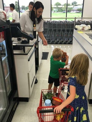 Young shoppers unload groceries out of their miniature shopping carts at the new Fareway store in Johnston.