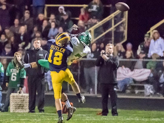 Climax-Scotts' Dylan Butler (12) breaks up a pass to Mendon's Ruben Vorster (7) during the 2016 MHSAA Division 8 playoffs.