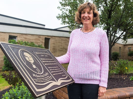 Cheryl Calvert poses for a photo with plaque for Melissa
