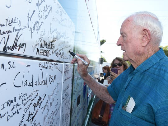 Father Joseph Breen signs the outside of the Nuns on