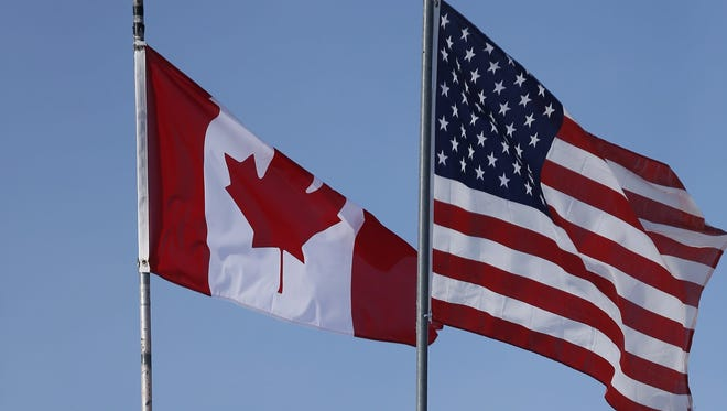 In this Feb. 9, 2017, file photo, an American flag and a Canadian flag fly above Maple Leaf Motel's office in Emerson, Manitoba.