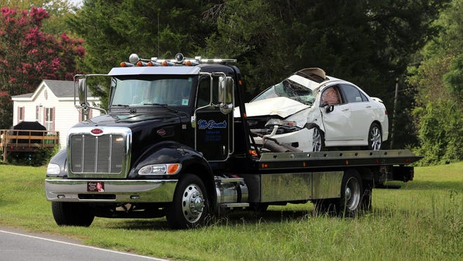 A car is taken away from the scene of a wreck along Polkville Road on Tuesday.