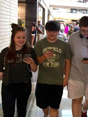 Mia Melugin, 13, her brother Liam Melugin, 16, and their friend Joshua Loughren, 16, play Pokemon Go while walking around the NorthGate Center mall in Dallas.