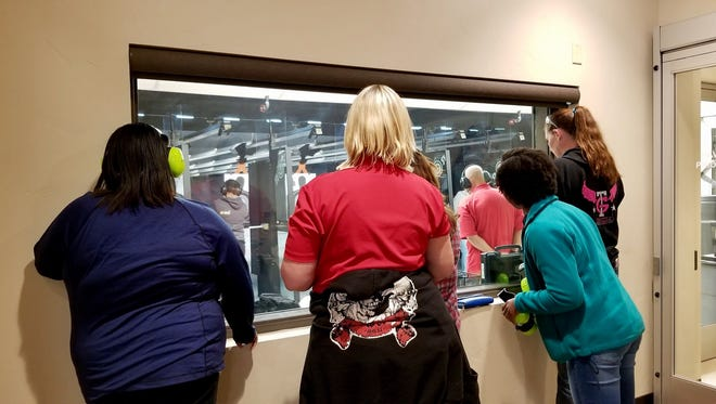 A group of women peer in through a window at other students learning to shoot during a firearms class at the Reno Guns & Range.