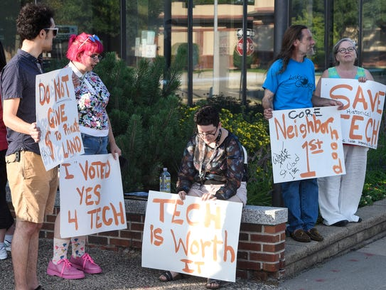 People hold signs in support of repurposing Tech High