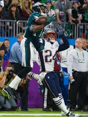 Eagles' Alshon Jeffrey jungles a pass that would go on to be intercepted while under pressure from New England's Stephon Gilmore Sunday at US Bank Stadium.