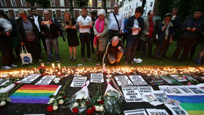 People lay candles and floral tributes at a flower laying service at Saint Anne's Church in Soho, London, Monday June 13, 2016, following a vigil for the victims of Sunday's Orlando shootings at a Gay nightclub in Florida. Wielding an AR-15 semi-automatic rifle and a handgun, Omar Mateen, a 29-year-old American-born Muslim, opened fire at the crowded Pulse Orlando club early Sunday, killing dozens and wounding others. (Yui Mok/PA via AP)  UNITED KINGDOM OUT  NO SALES NO ARCHIVE