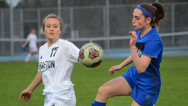 Whitefish Bay's Molly Keiper plays the ball while Grafton's Ava Pedersen defends.