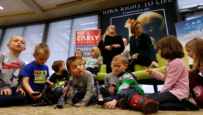 Mason De La Garza, 4, plays with a TV camera mic as a group of students from the My Learning Safari preschool gather around Republican presidential candidate Carly Fiorina Wednesday, Jan. 20, 2016, at the Greater Des Moines Botanical Gardens. The preschoolers from Ankeny were on a field trip at the botanical gardens when Fiorina invited them to join her during her appearance with Iowa Right to Life.