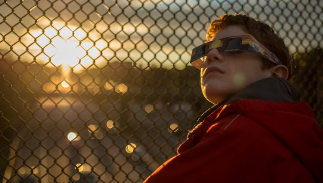 In this handout photo provided by NASA, Alex Frye, 12, uses special viewing glasses to look at a partial solar eclipse from a highway overpass October 23, 2014, in Arlington, Virginia. These type of special glasses are recommended to view the total solar eclipse on Aug. 21, 2017.