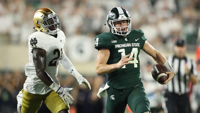 Michigan State's Brian Lewerke runs for a long gain in the first quarter as Notre Dame's Jalen Elliott gives chase at Spartan Stadium on Sept. 23, 2017 in East Lansing.