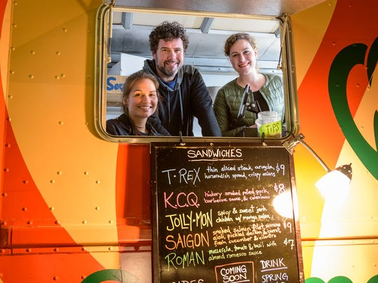 Jenn Eldreth, Mike Stanley, and Elyssa Klett in the serving window of the WiLDWiCH food truck Saturday night as they await late night customers. as they wait for the Halloween Loop customers.