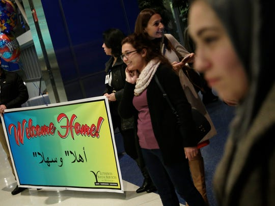 Members of Lutheran Social Services of Michigan and members of the Syrian community wait for Refaai Hamo, 54, a scientist Syrian refugee, to arrive at Detroit Metropolitan Wayne Country Airport with his four children on Thursday, Dec. 17, 2015, in Romulus.