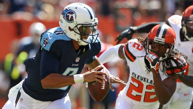Tennessee Titans quarterback Marcus Mariota (8) against Cleveland Browns defensive back Tramon Williams (22) during an NFL football game, Sunday Sept. 20, 2015, in Cleveland. (AP Photo/Ron Schwane)
