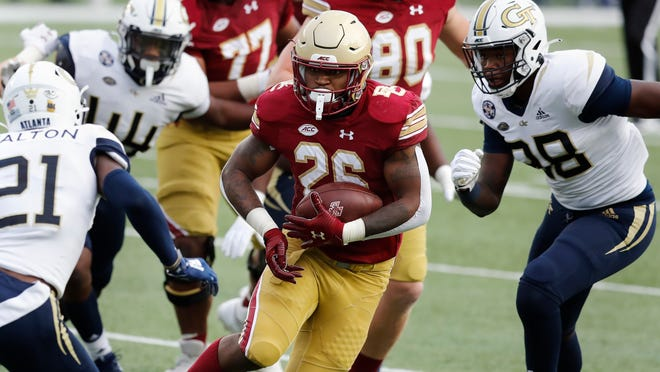 Boston College running back David Bailey carries the ball against Georgia Tech defensive back Zamari Walton (21) and defensive lineman Curtis Ryans, right, during the first half at Chestnut Hill.