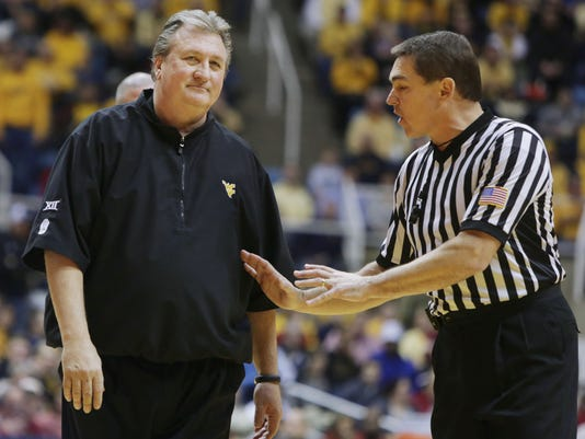 West Virginia head coach Bob Huggins, left, talks with a referee during the second half of an NCAA college basketball game, Saturday, Jan. 10, 2015, in Morgantown, W.Va. Iowa defeated West Virginia 74-72. (AP Photo/Raymond Thompson)