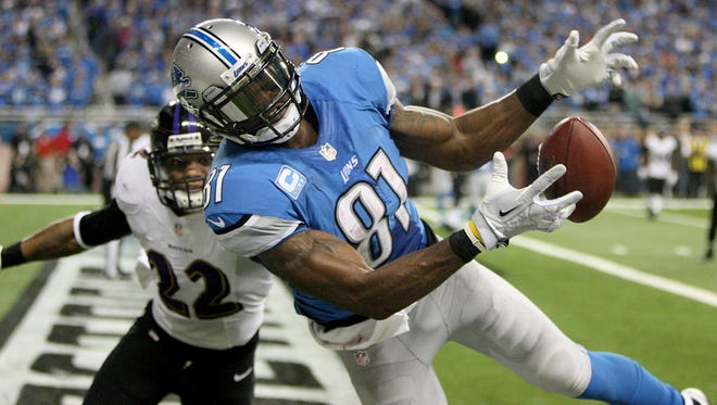 Detroit Lions wide receiver Calvin Johnson, right, drops a pass while defended by Baltimore Ravens cornerback Jimmy Smith on Dec. 16, 2013, at Ford Field in Detroit.