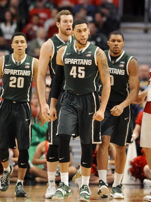 MSU's Travis Trice, Matt Costello, Denzel Valentine and Marvin Clark Jr., right, celebrate a defensive stop against Wisconsin n their Big Ten tournament championship game Sunday in Chicago.