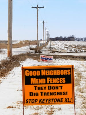 In this March 11, 2013 photo, signs opposing the Keystone XL pipeline are seen along its planned route, near Bradshaw, Neb.