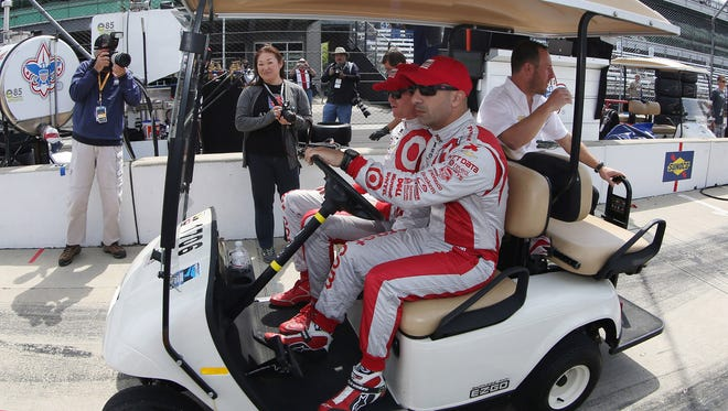 IndyCar Series driver Tony Kanann drives a golf cart with Scott Dixon during practice for the Indianapolis 500 at the Indianapolis Motor Speedway.