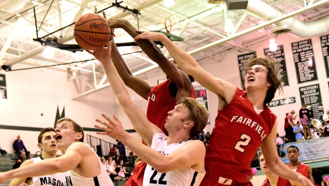 A battle for the boards rages under the Mason goal as Matt King (22) of Mason draws and over the back foul from Fairfield's Drew O'Donnell,  January 20, 2017 -- Geoff Blankenship for The Enquirer