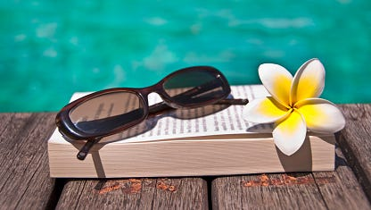 Book and sunglasses, blue water, background