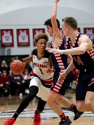 New Albany's Romeo Langford drives around two Bedford North Lawrence defenders.