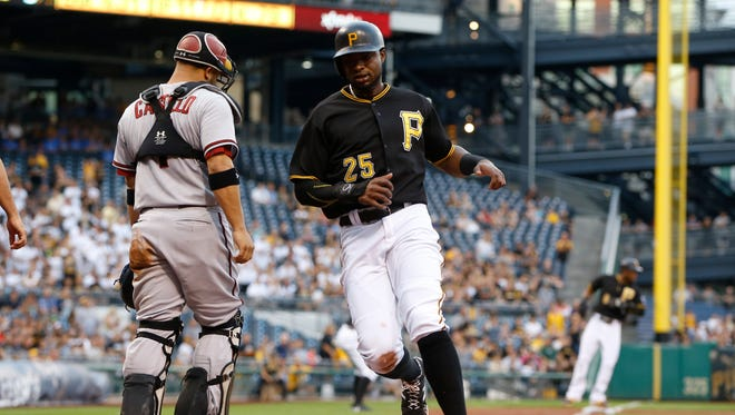 Pittsburgh Pirates' Gregory Polanco crosses the plate past Arizona Diamondbacks catcher Welington Castillo after scoring on a sacrifice fly by Andrew McCutchen in the first inning of a baseball game, Tuesday, Aug. 18, 2015, in Pittsburgh.