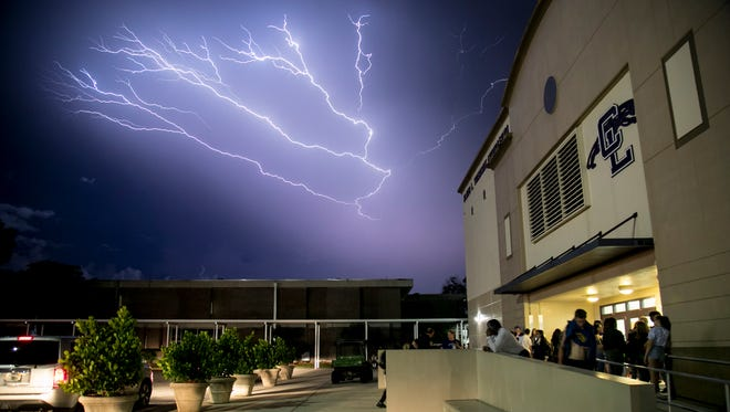 Lightning fills the sky over Cypress Lake High School's gym after a preseason game against Riverdale was cancelled in 2017.