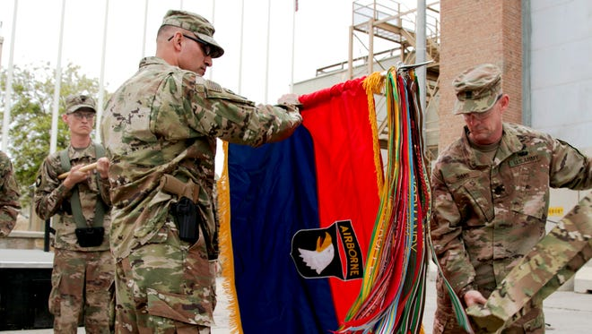 Maj. Gen. Andrew Poppas, 101st Airborne Division commander, and Command Sgt. Maj. Todd Sims, 101st senior enlisted leader, unfurl the division headquarters' colors, April 15, during a transfer of authority ceremony at Bagram Airfield, Afghanistan.