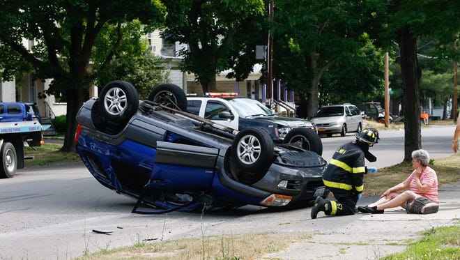A firefighter speaks with a woman at East Washington Avenue and Oak Street where one car rolled over in a two-car collision.