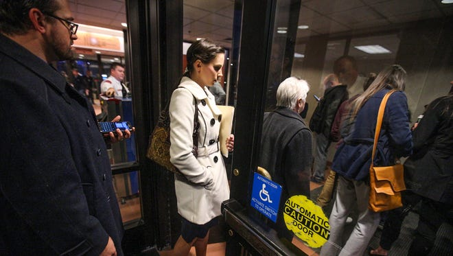 Rachael Denhollander and her husband, Jacob, left, enter the security line inside Ingham County Circuit Court in Lansing, Mich., Wednesday, Jan. 24, 2018.