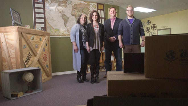 From left, data specialist Janice Yezback, special projects coordinator Sarah Stidham, executive director the Rev. Jason Woolford and warehouse manager Mitch Brockway stand in front of a map featuring push pins which indicate locations where Christian Resources International has shipped Christian literature free of charge.