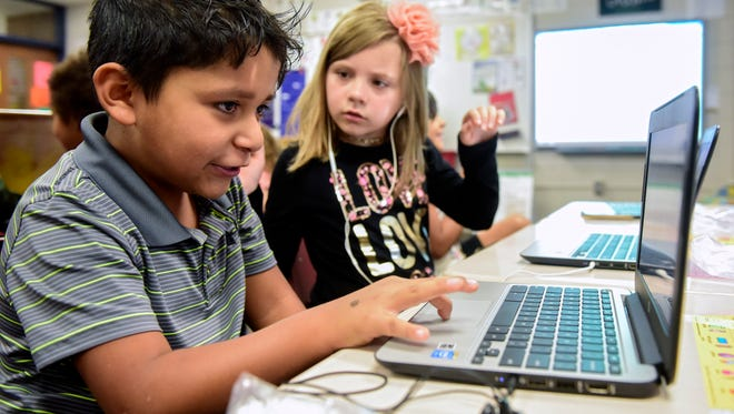 Kyler Meng (left), a second-grader at Lowell Elementary School, explains how he made his coding project work to classmate Jade Engels (right) in class on Thursday, Sept. 28, 2017. Lowell is one of three elementary schools in Sioux Falls participating in a new coding immersion program where students learn computer coding for 30 minutes a day.