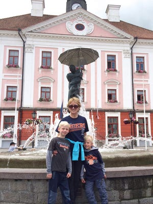 Rosalee Tithof of Saginaw and  her 2 grandsons, Truman, 8, and Lawrence, Danek, 6, of Chesaning, pose with the D to the town square of Tartu, Estonia in front of the Kissing Students sculpture and fountain.