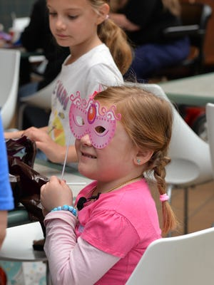 Wearing her princess mask, 6-year old Maya Richardson, of Lebanon, enjoys presents received while spending the afternoon at Hershey's Chocolate World on Saturday, April 23, 2016. After viewing a 4-D movie and Hershey treats, Maya received a shopping cart filled with gifts and the itinerary for her upcoming trip to Disney World, Sea World, and Universal Studios courtesy of Make-A-Wish.