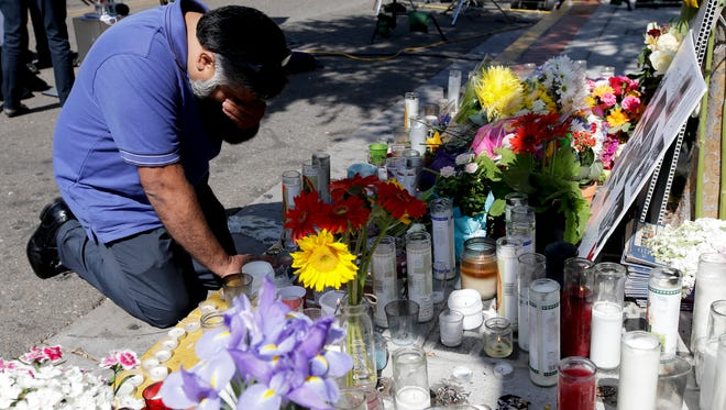 Jose Cardoso pays his respects at a makeshift memorial in front of the IV Deli Mart, where part of Friday night's mass shooting took place by a drive-by shooter, on May 25, 2014, in the Isla Vista area near Goleta, Calif.