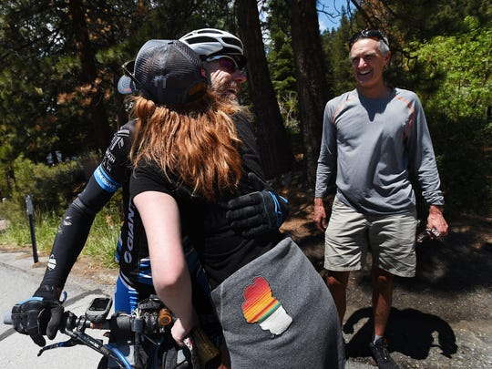Endurance athlete Blake Bockius gets a hug from his daughter Emma after completing the Comstock EPIC backpacking race at the California/Nevada border near Lake Tahoe in Crystal Bay on May 26, 2015. Bockius completed the 550 mile route across Nevada, from Baker to Crystal Bay, in just over three days. Bockius' friend Todd Huckins is seen on the right.