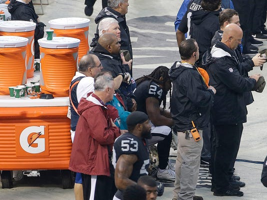Oakland Raiders running back Marshawn Lynch (24) is surrounded by officials as he sits during the national anthem before an NFL football game against the Denver Broncos in Oakland, Calif., Sunday, Nov. 26, 2017. (AP Photo/Jeff Chiu)