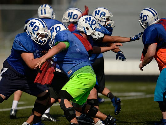 Green Bay Notre Dame linemen battle it out during football practice.