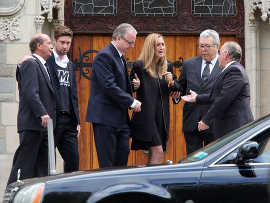 Donna Hall is led to a waiting car after the funeral