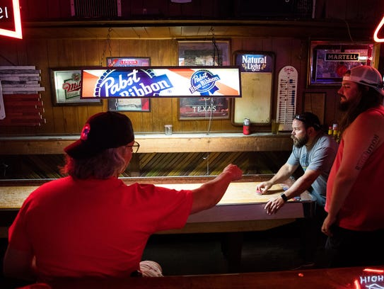 A group of customers plays shuffleboard at Vernon's