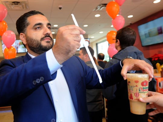 Dunkin' Donuts franchisee Aharon Aminpour helps with coffee orders during the opening of the Westlake Village location in 2016.