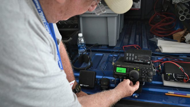"""Randy Harris tunes his radio to find other amateur operators — also known as """"hams"""" — participating in the American Radio Relay League's international Field Day."""