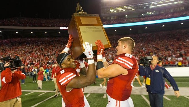 Wisconsin Badgers running back Corey Clement (6) and tight end Troy Fumagalli (81) lift the Freedom Trophy after beating Nebraska.