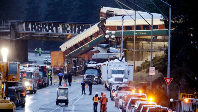 Lights illuminate cars from an Amtrak train that derailed above Interstate 5, Monday, Dec. 18, 2017, in DuPont, Wash. The Amtrak train making the first-ever run along a faster new route hurtled off the overpass Monday near Tacoma and spilled some of its cars onto the highway below, killing several people, authorities said.