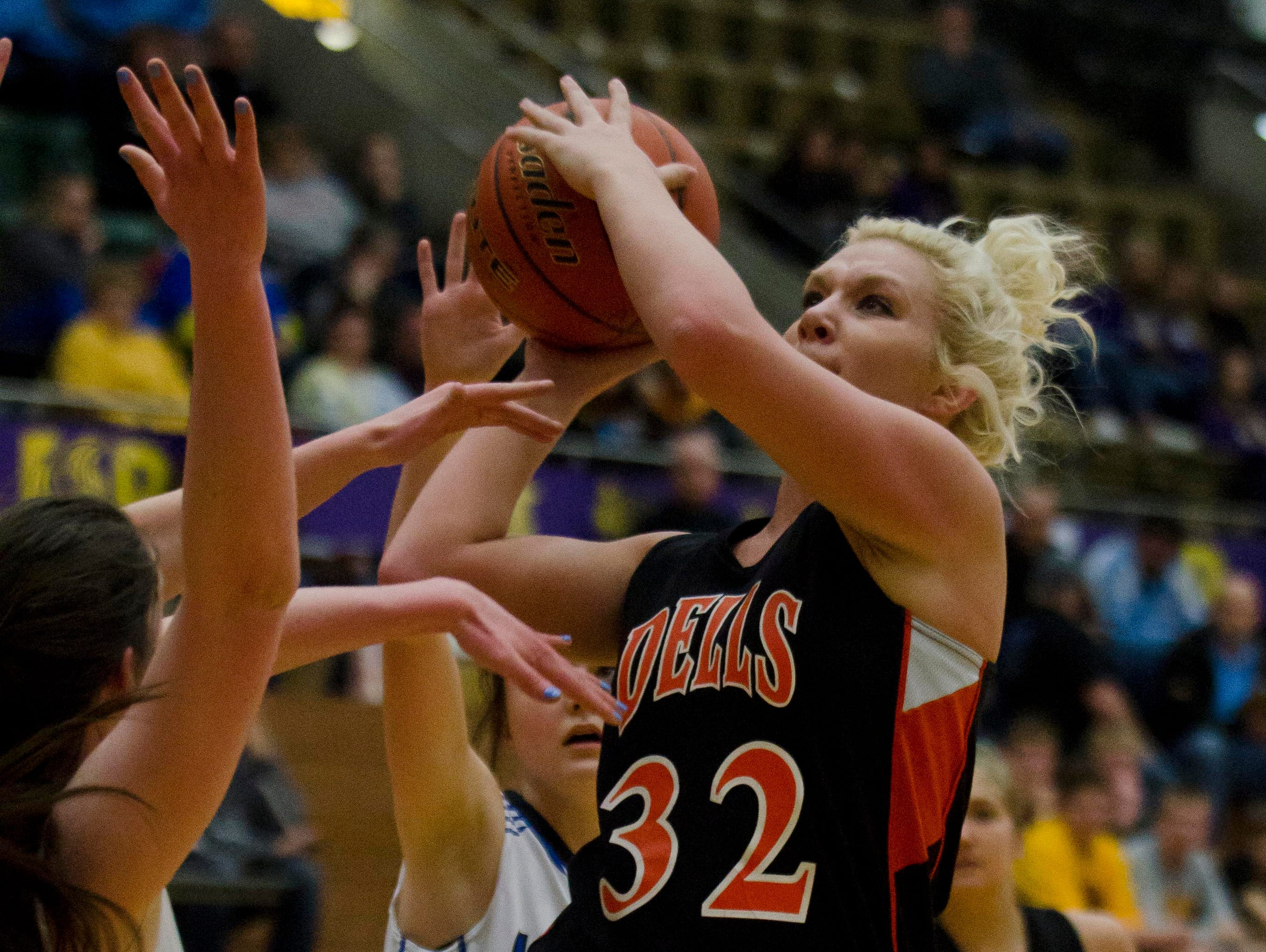 Mikaela Stofferahn of Dell Rapids shoots over a St. Thomas More defender Thursday, March 10, in the Class A state quarterfinals at Watertown Civic Arena.