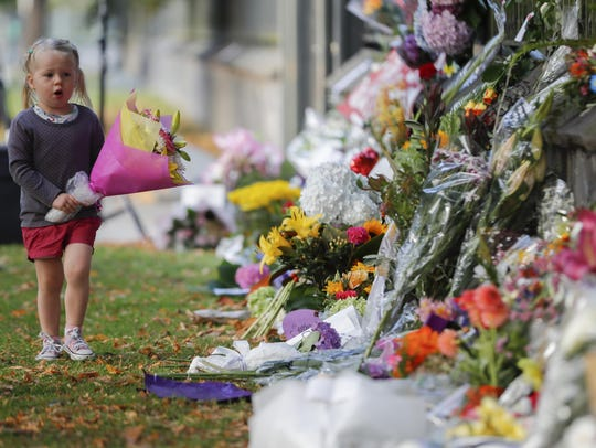 A girl carries flowers to a memorial wall following